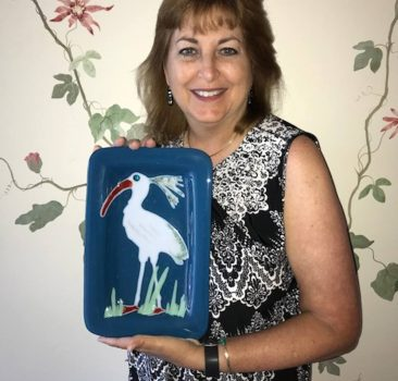 Jeanne Risher holding her art