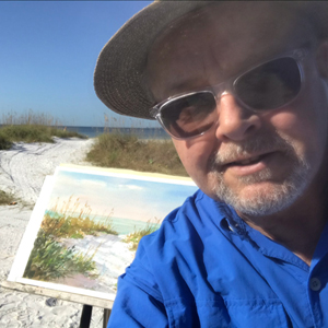 A photo of Keith painting on the beach