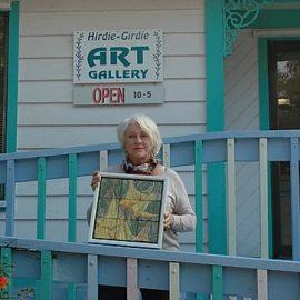 Sue Housler standing in front of the Hirdie Girdie Gallery holding one of her works of art