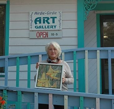 Sue Housler standing in front of the Hirdie Girdie Gallery holding one of her works of art