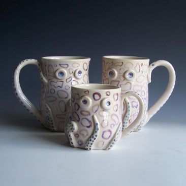 Two insanely cute octopus mugs and one smaller octopus espresso mug. Large mugs are about five inches tall and three and a half inches wide. Seven small legs with suction cups attached at the base and against the bottom of the mugs. The eighth leg is the handle and connects from the bottom of the mug to the rim on the top. All mugs have two eyes. Glazed with irregular blue rings under a white glaze. Made by Kelly Williamson, professional potter.