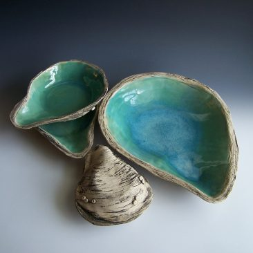 Five piece ceramic serving bowl set in the shape of oysters. Glazed glossy seagreen inside and glazed with a matte black stain wash in the textured crevices on the bottom. The bottom of all the dishes has about nine decorative clay barnacles attached and various textures to resemble the look and feel of a real oyster shell. The large dish is over twelve inches long and twelve inches wide. The two medium sized bowls are about eight inches long and six inches wide. The two smallest bowls are about six inches long and four inches wide. Made by Kelly Williamson, professional potter.