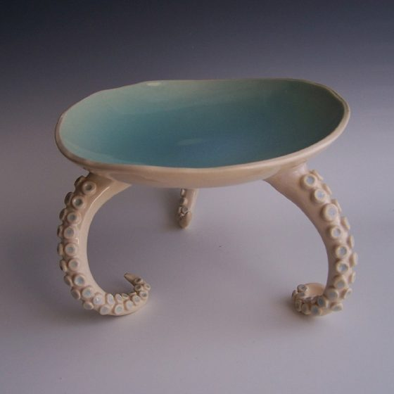 Serving tray with three octopus legs. The total height and width is about eight inches. Each leg has about thirty small balls of clay attached for suction cups. Glazed on the inside of the plate and on the inside of each suction cup with a glossy turquoise blue. The rest of the legs and the underside of the plate is glazed with a clear glossy glaze. Made by Kelly Williamson, professional potter.
