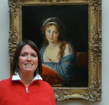 Julie Griffin standing in front of one of her masterpieces. Julie is wearing a red sweater and has dark brown hair. The painting behind her is a repruction of an original painting of a woman with a gold frame.