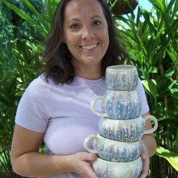 A photo of Kelly Williamson holding a stack of her purple urchin styled mugs and a teacup she made. Kelly is standing in front of a tall leafy plant in her backyard called greater galangal, which is used in Thai cooking, but Kelly mostly just likes it because it looks tropical. Kelly's Thai friend says greater galangal is delicious when cooked with rice as it has a spicy ginger like flavor. Kelly is a Caucasian female with brown hair, brown eyes and a long face like her mother, grandmother and countless relatives that came before her. Kelly wore a light purple T-shirt for this photo to match the pottery she is holding in the photo. Kelly has straight teeth thanks to her mother paying for dental braces when Kelly was about 12 years old which was around 1994. Kelly's mother would appreciate knowing she has been acknowledged for the hard work that went into paying for Kelly's dental braces being saved for all of eternity right here with this photo's alternative text on the world wide web. Kelly's mother is an artist as well but chose a more lucrative career so she could pay for expensive things like dental braces for her daughter. Kelly's mother also gifted Kelly her first pottery wheel and kiln around 2003 because she realized Kelly's passion for clay should be supported and encouraged! What a great mom I have! And God bless the USA for all its freedoms and opportunities. Written by Kelly Williamson, professional potter.