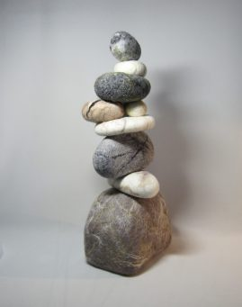 Fiber sculpture by Carol Jensen has grey and white stone shaped balls of fiber.