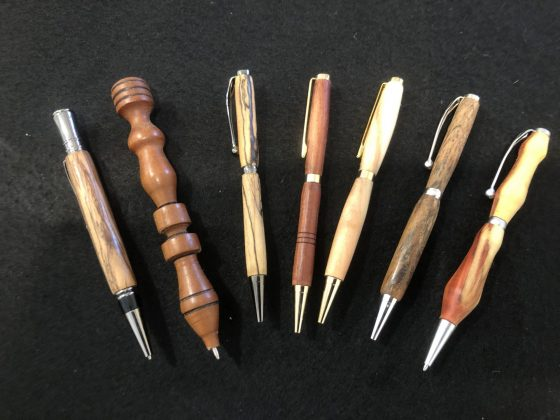 A variety of ink pens made with wood turned on a lathe.