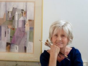 A photo of Priscilla Jeffcoat holding paintbrushes in front of a cityscape watercolor painting.