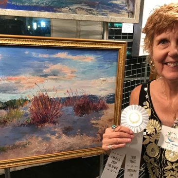 A photo of Judy Usavage holding a white ribbon in front of a sand dune painting