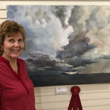 judy usavage with her award winning painting of a stormy sky